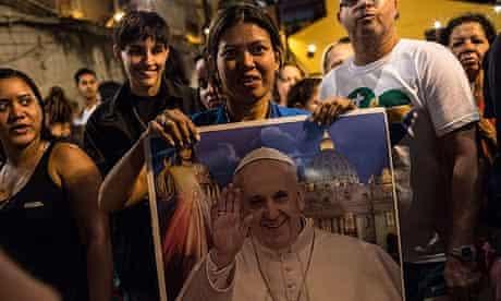 A Brazilian holds a portrait of Pope Francis after a mass in Rio de Janeiro's Rocinha shantytown