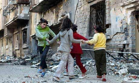 Children play in front of their homes in Khaldiyeh district in Homs
