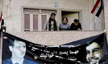 Syrians in Homs above a poster of Bashar al-Assad, left, and Hassan Nasrallah, leader of Hezbollah