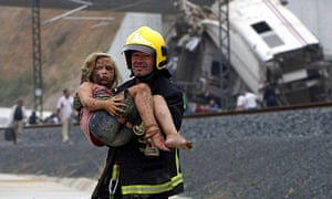 A firefighter carries an injured girl from the wreckage of the Santiago de Compostela train crash