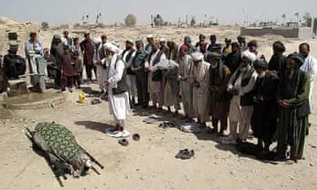 Mourners in Lashkar Gah pray near the body of Lieutenant Nigara, the senior policewoman in Helmand
