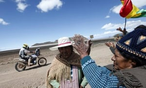 One of the participants in the Dakar rally passes indigenous people between Bolivia, and Chile