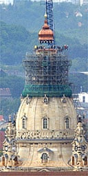 The new cupola of Dresden's Frauenkirche being lowered into place