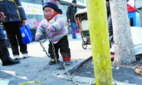 A 2 year old Chinese boy is chained to a post on roadside
