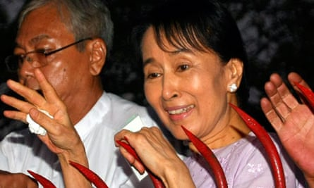Aung San Suu Kyi waves to supporters gathered outside her house after her release in Yangon