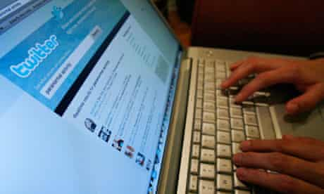 A Twitter page is displayed on a laptop computer