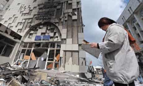 A woman walks by the burnt out offices of the general prosecutor in Bishkek, Kyrgyzstan