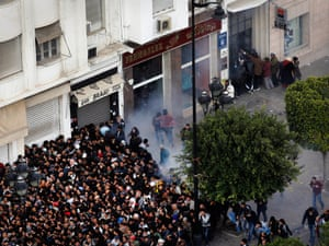 Demonstrators move away from tear gas used by police in Tunis