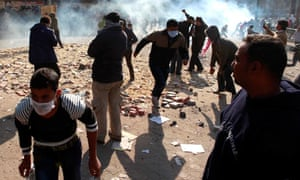 Protesters run away from tear gas fired by riot police near Tahrir Square in Cairo