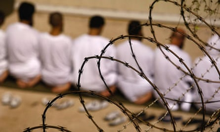 A group of detainees kneels during prayers at Guantanamo Bay