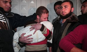 Jihad Misharawi holds the body of his 11-month son, Ahmad