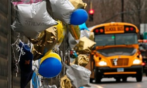 A school bus rolls towards a memorial for victims of the school shooting in Newtown