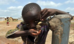 A boy drinks from a water tap in Sierra Leone