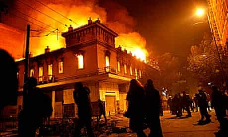 Protesters pass by a burning cinema in Athens