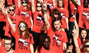 A crowd of young people wearing Kony 2012 T-Shirts make the peace sign