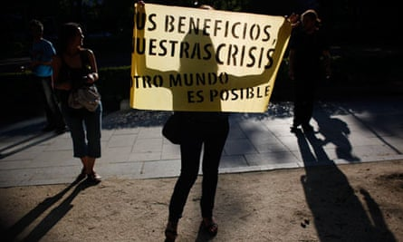 A woman holds a banner against capitalism in Madrid