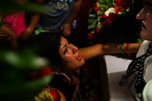 A young woman weeps in front of a bust of Jesús Malverde in Culiacán, Sinaloa