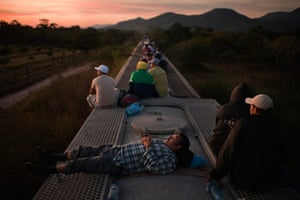 Central American migrants in Chiapas ride on top of a freight train