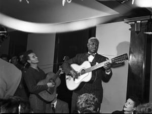 Musicians Woody Guthrie and Lead Belly (Huddie Ledbetter) perform surrounded by an audience in photo