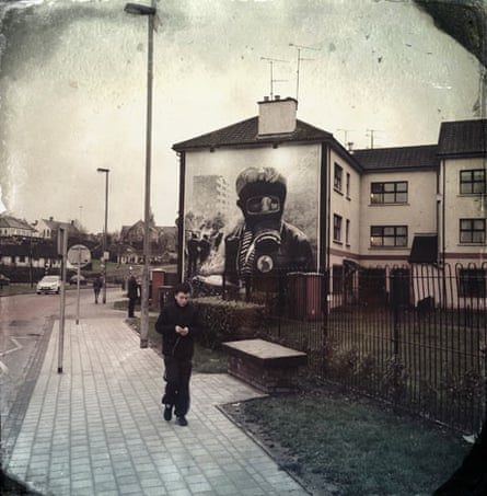 A young boy walks in front of the Petrol Bomber Mural in Derry