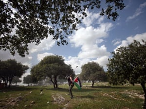 A Palestinian youth uses his sling shot to lob a stone in Bilin