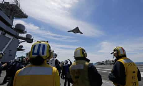 A Navy x-47B drone does a fly buy the nuclear powered aircraft carrier USS George HW Bush