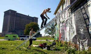 Artists paint the walls of Imagination Station, a house across from Detroit's abandoned train depot.