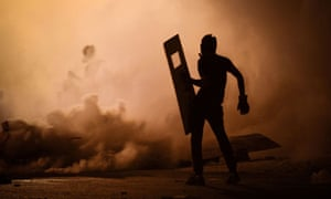 A Bahraini protestor stands amidst tear gas fired by riot police in Diraz