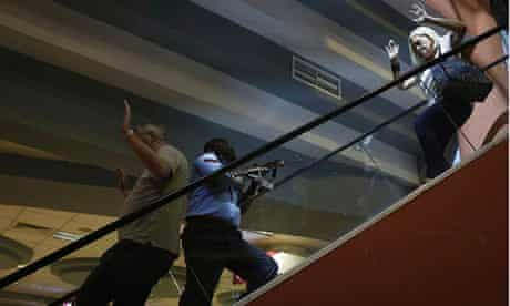 A police officer secures an area as civilians flee inside Westgate Shopping Centre in Nairobi