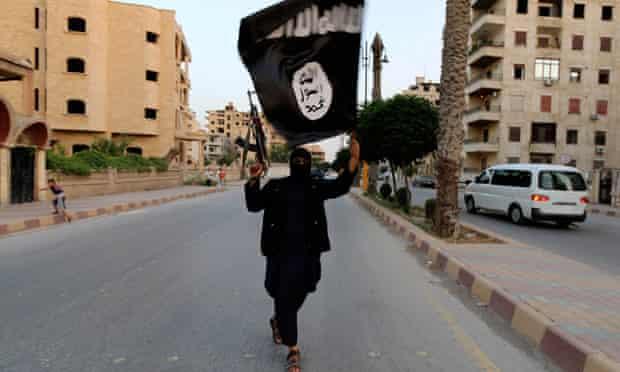 Isis member waves flag in Raqqa