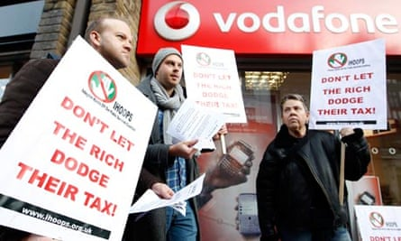 Demonstrators stand outside a branch of Vodafone in tax protest