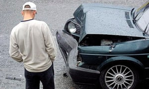 A Young Male Driver Looking At Damage To His car