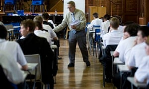 An exam invigilator hands out question papers before a GCSE