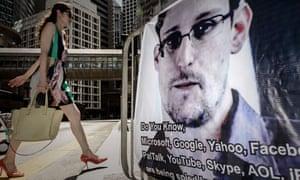 Woman walks past Edward Snowden banner in Hong Kong