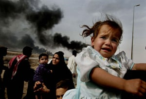 Great press photography: The terror is etched across this girl's face as a family flee Basra, 2004