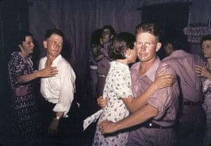 Great press photography: reddened faces start out of the shadows of a country dance in the midwest
