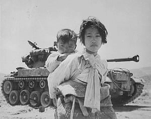 Great press photography: A young girl carrying her brother passes a stalled US M-26 Pershing tank.