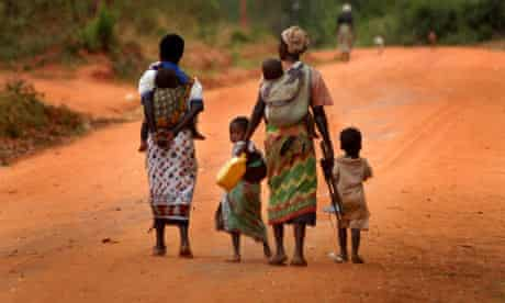 A family walks down a dusty road in Africa