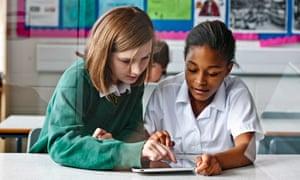 wo girls in classroom using iPad