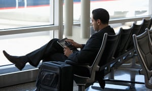 Business traveler using tablet computer in airport.