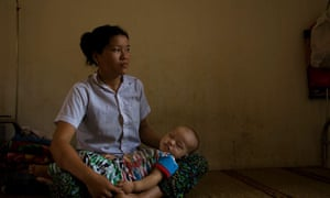 A woman waits with her baby to see a doctor at a clinic in Hoa Binh province