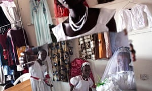 Bride Esther Birungi, 20, looks at herself in the mirror held by her sister