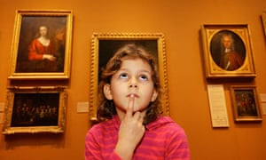 A kid looks up at a painting