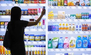 A supermarket customer in Korea uses a mobile phone to loaded with credit card data to buy items