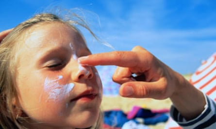 Girl having sun block applied to cheeks and nose