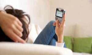 Woman with smartphone lying on a couch.