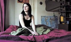 Girl sitting cross-legged on a bed