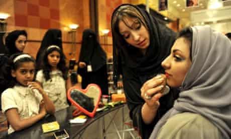 A Saudi woman applies makeup