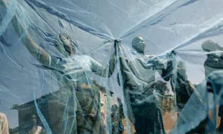 Villagers on Zambia look at new mosquito nets