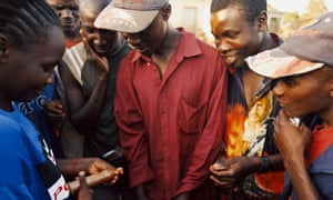 An aid worker demonstrates to a group of young men how to use a condom.